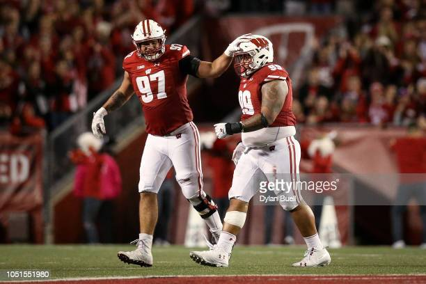 Isaiahh Loudermilk and Olive Sagapolu of the Wisconsin Badgers celebrate after recovering a fumble in the third quarter against the Nebraska...