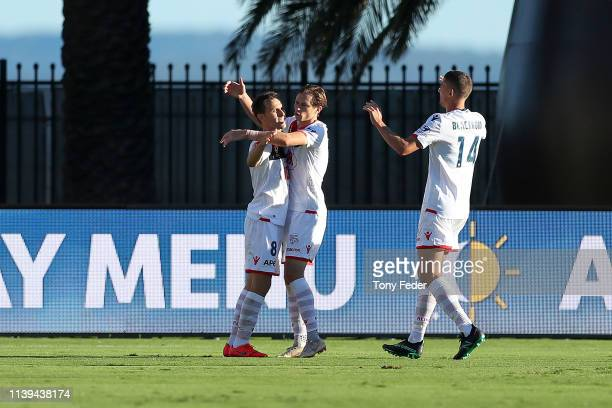 Isaias of Adelaide United celebrates a goal with team mate Graig Goodwin during the round 23 ALeague match between the Central Coast Mariners and...