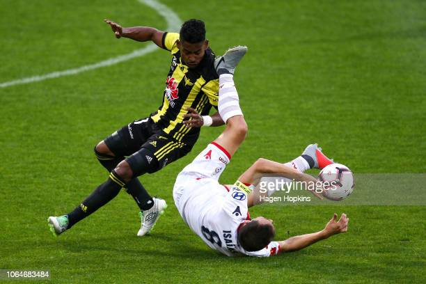 Isaias of Adelaide United loses his footing in the challenge of Roy Krishna of the Phoenix during the round five ALeague match between the Wellington...