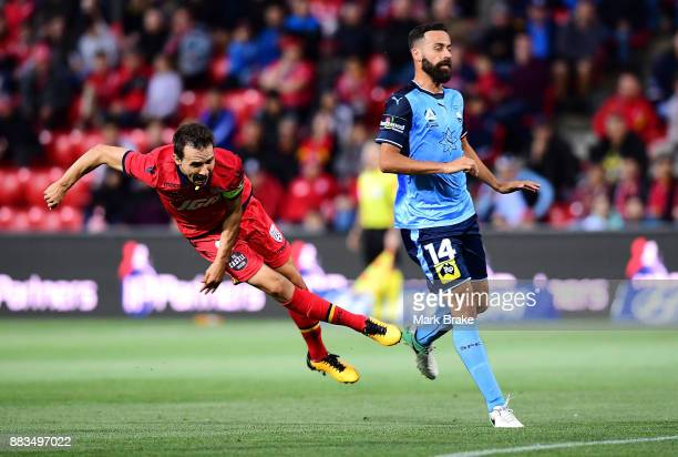 Isaias of Adelaide United stumbles as he shoots for goal past Alex Brosque of Sydney FC during the round nine ALeague match between the Adelaide...