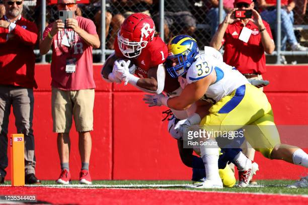 Isaih Pacheco of the Rutgers Scarlet Knights is tackled by Johnny Buchanan of the Delaware Blue Hens as he dives into the end zone for a touchdown...