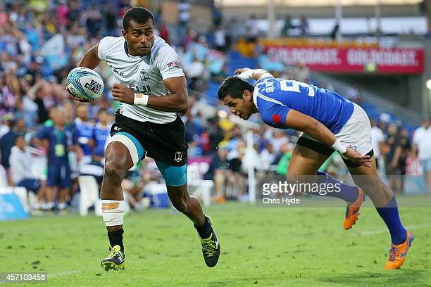 Isake Katonibau of Fiji makes a break to score a try during the 2014 Gold Coast Sevens Cup final match between Fiji and Samoa at at Cbus Super...