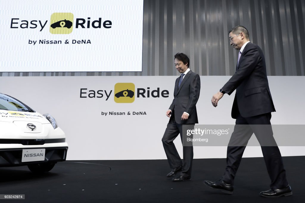 Isao Moriyasu, president and chief executive officer of DeNA Co., left, and Hiroto Saikawa, president and chief executive officer of Nissan Motor Co., prepare for a photo session during a news conference for the 'Easy Ride' robot taxi service, jointly developed by Nissan and DeNA, at the Nissan global headquarters in Yokohama, Japan, on Friday, Feb. 23, 2018. The service, which allows the public to use a smartphone app to book 15-minute rides, is scheduled to launch on March 5 for two weeks in Yokohama. Photographer: Kiyoshi Ota/Bloomberg via Getty Images