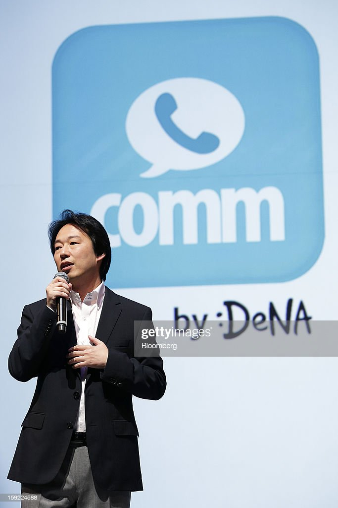 Isao Moriyasu, president of DeNA Co., speaks in front of the logo for Comm, the company's free calling app, during a news conference in Tokyo, Japan, on Thursday, Jan. 10, 2013. DeNA will offer music services for iOS and Android platforms within this fiscal year, according to a statement today. Photographer: Kiyoshi Ota/Bloomberg via Getty Images
