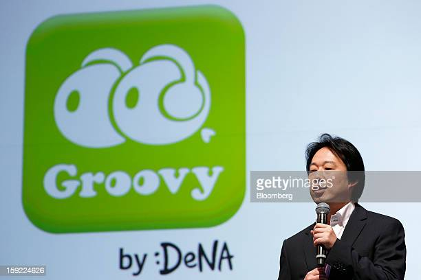 Isao Moriyasu president of DeNA Co speaks in front of the logo for Groovy the company's social music app during a news conference in Tokyo Japan on...