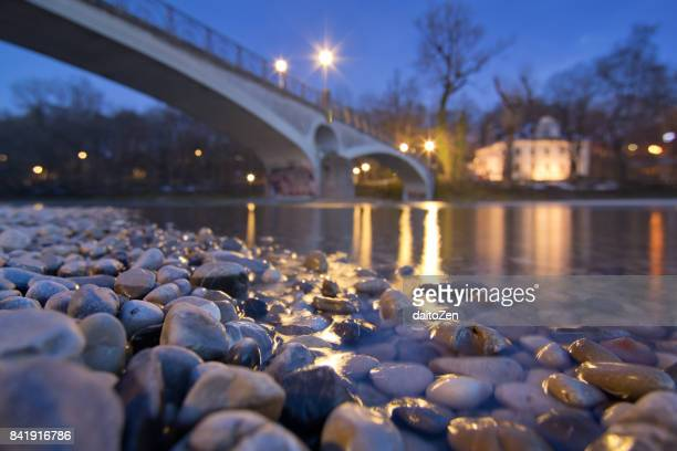 isar river shore with pebble stones and kabelsteg pedestrian bridge,  munich, bavaria, germany, europe - fiume isar foto e immagini stock