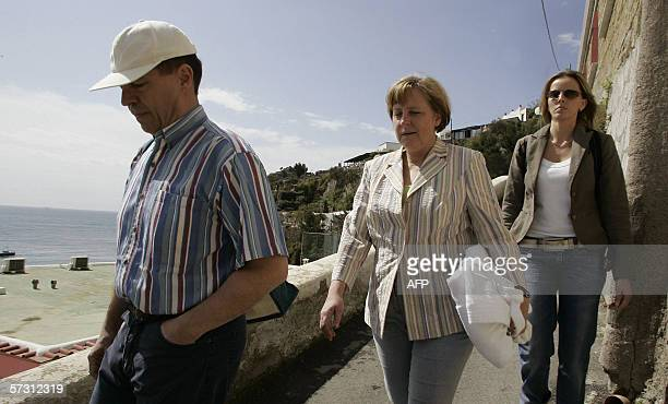 CORRECTION NAME Germany's chancellor Angela Merkel walks with her husband Joachim Sauer in the little streets of Sant'Angelo 11 Avril 2006 as she...