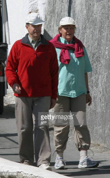 Germany's chancellor Angela Merkel walks with her husband Joachim Sauer in the little streets of Sant'Angelo 12 Avril 2006 as she spends two weeks of...