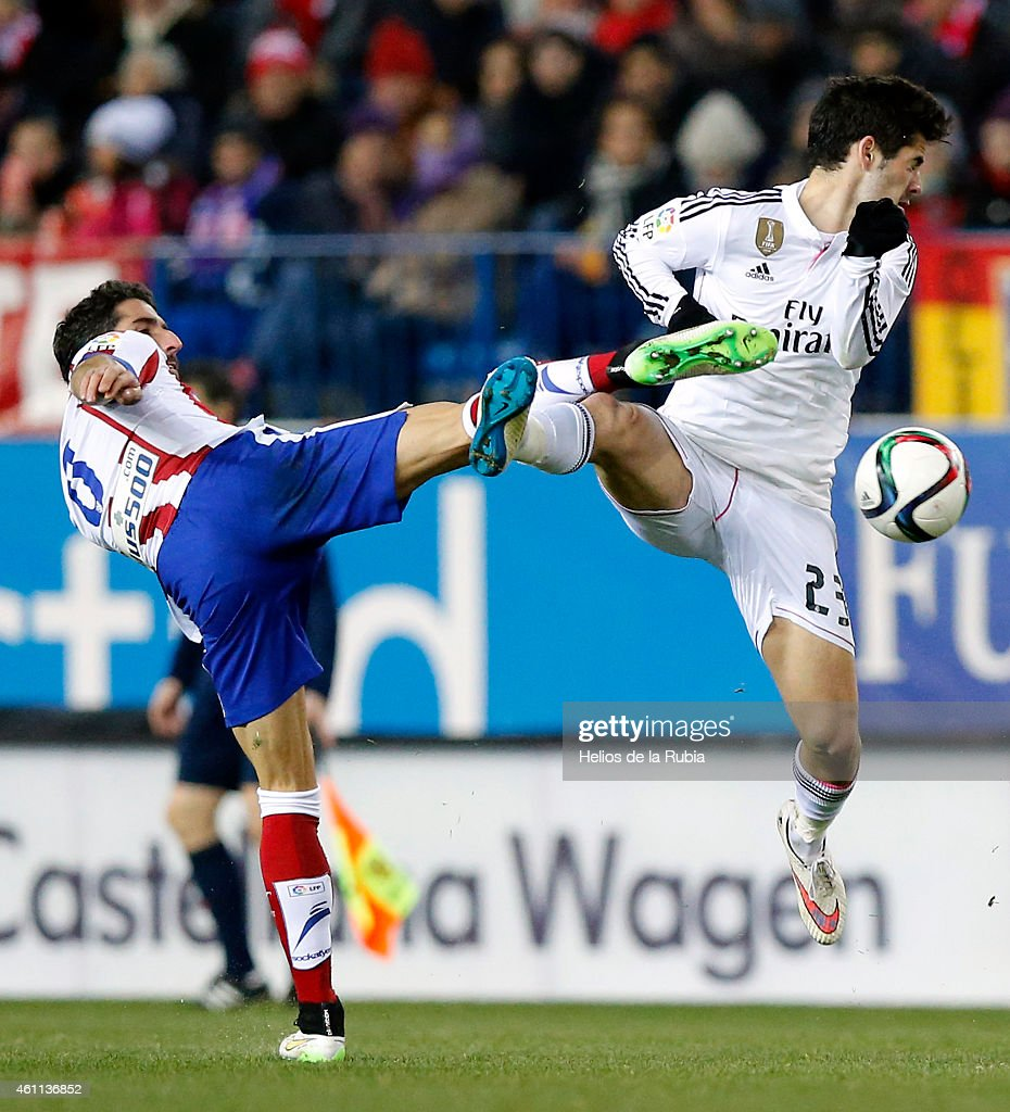 Isco Alarcon (R) of Real Madrid and Raul Garcia of Atletico de Madrid compete for the ball during the Copa del Rey, round of 16 first leg match between Club Atletico de Madrid and Real Madrid CF at Vicente Calderon Stadium on January 7, 2015 in Madrid, Spain.