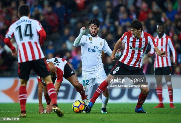 Isco Alarcon of Real Madrid CF being followed by Mikel Rico of Athletic Club and Mikel San Jose of Athletic Club during the La Liga match between...