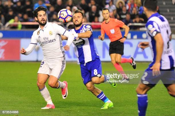 Isco of Real Madrid and Emre Colak of Deportivo vie for the ball during the Spanish league football match between Deportivo and Real Madrid at the...