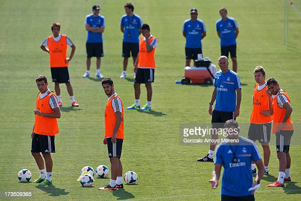 Isco of Real Madrid and his teammates Nacho Karim Benzema Asier Illarramendi and head coach Zinedine Zidane listen to a Real madrid coach during the...