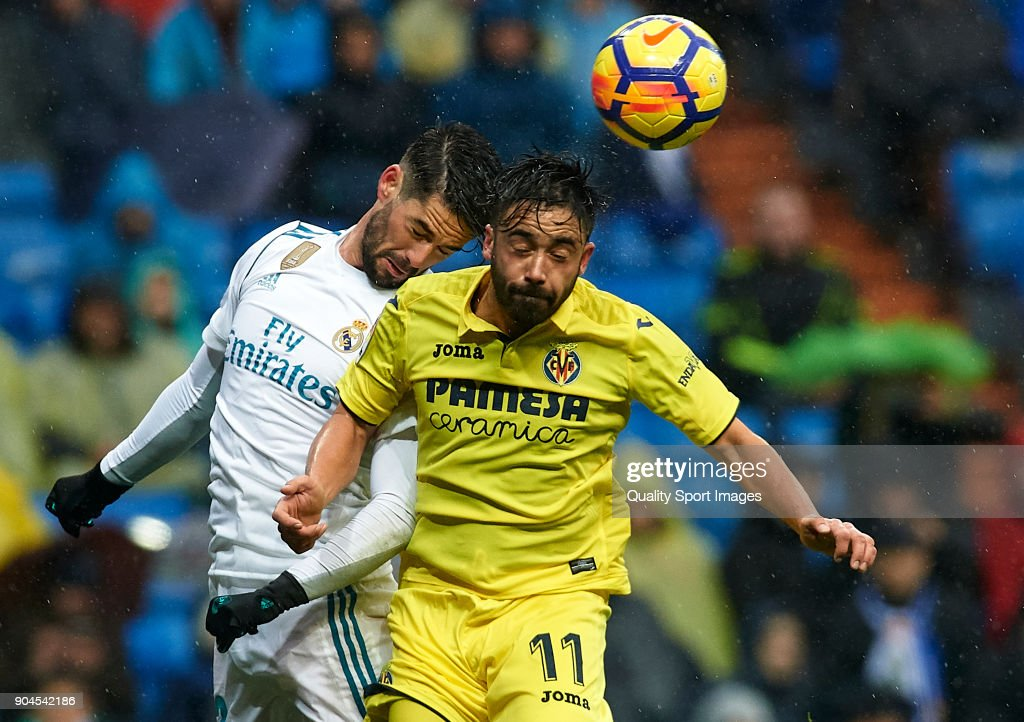 Isco of Real Madrid competes for the ball with Jaume Costa (R) of Villarreal during the La Liga match between Real Madrid and Villarreal at Estadio Santiago Bernabeu on January 13, 2018 in Madrid, Spain.