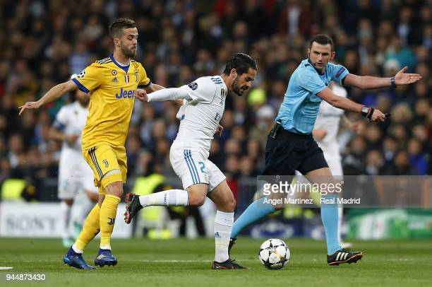 Isco of Real Madrid competes for the ball with Miralem Pjanic of Juventus during the UEFA Champions League Quarter Final Leg Two match between Real...