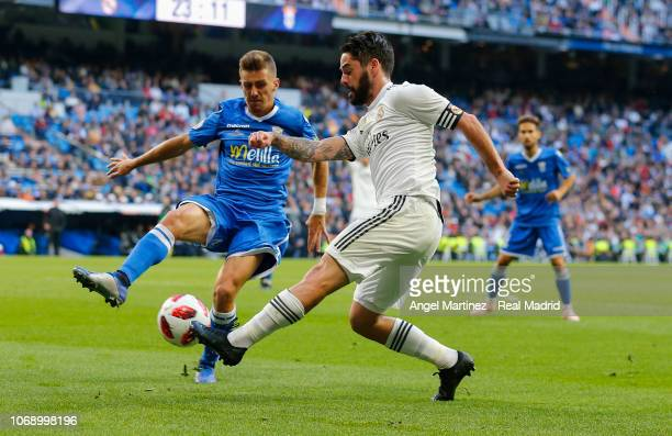 Isco of Real Madrid competes for the ball with Pepe Romero of Melilla during the Copa del Rey fourth round second leg match between Real Madrid and...