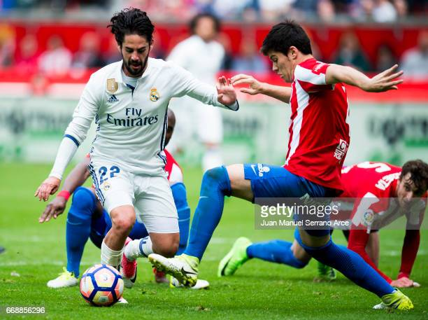 Isco of Real Madrid duels for the ball with Jorge Mere of Real Sporting de Gijon during the La Liga match between Real Sporting de Gijon and Real...