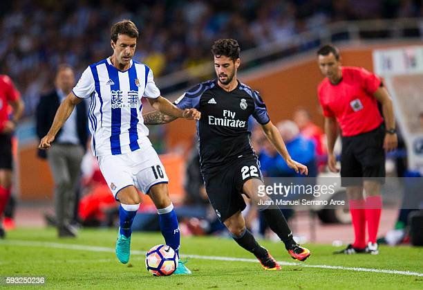 Isco of Real Madrid duels for the ball with Xabier Prieto of Real Sociedad during the La Liga match between Real Sociedad de Futbol and Real Madrid...