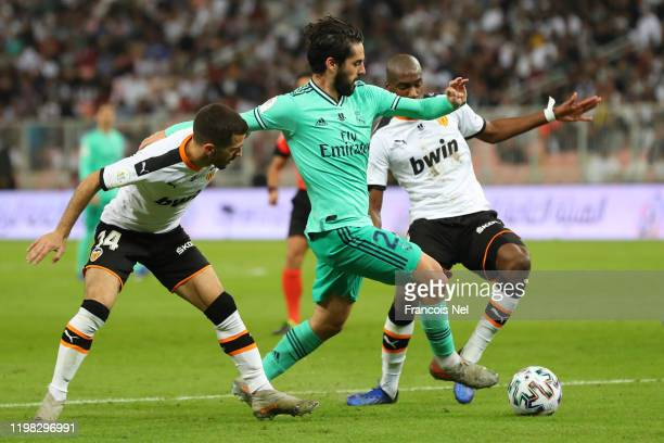 Isco of Real Madrid gets between Jose Luis Gaya and Geoffrey Kondogbia of Valencia during the Supercopa de Espana SemiFinal match between Valencia CF...