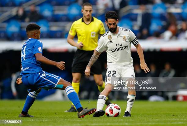 Isco of Real Madrid is challenged by Antonio Otegui of Melilla during the Copa del Rey fourth round second leg match between Real Madrid and Melilla...