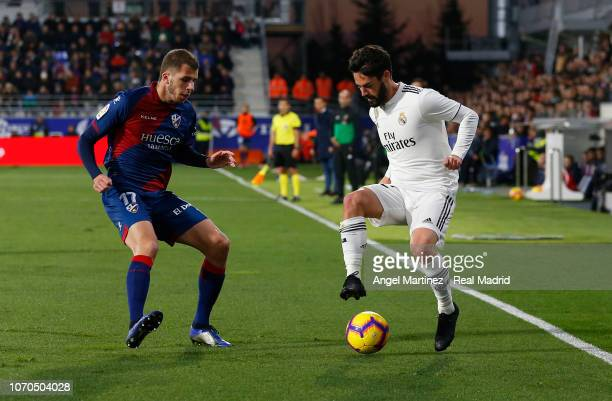 Isco of Real Madrid is challenged by Christian Rivera of SD Huesca during the La Liga match between SD Huesca and Real Madrid CF at Estadio El...