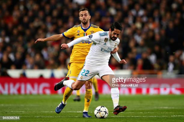 Isco of Real Madrid is challenged by Miralem Pjanic of Juventus during the UEFA Champions League Quarter Final second leg match between Real Madrid...