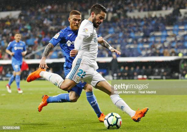 Isco of Real Madrid is challenged by Vitorino Antunes of Getafe during the La Liga match between Real Madrid and Getafe at Estadio Santiago Bernabeu...