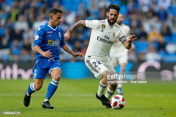 Isco of Real Madrid is chased by Juan Carlos Menudo of Melilladuring the Copa del Rey fourth round second leg match between Real Madrid and Melilla...
