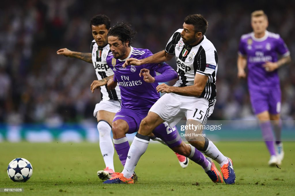 Isco of Real Madrid is fouled by Dani Alves of Juventus and Andrea Barzagli of Juventus during the UEFA Champions League Final between Juventus and Real Madrid at National Stadium of Wales on June 3, 2017 in Cardiff, Wales.