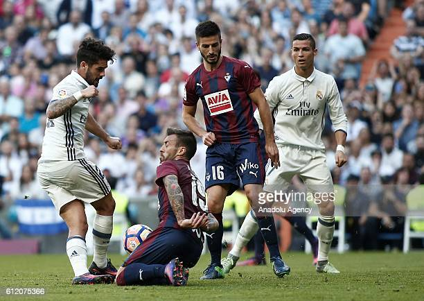 Isco of Real Madrid is in action against Antonio Luna of Eibar during the La Liga soccer match between Real Madrid CF vs Eibar at the Santiago...