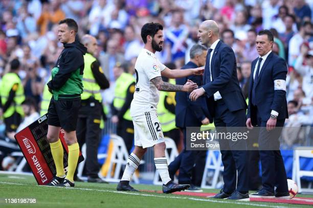 Isco of Real Madrid shakes hands with Zinedine Zidane MAanager of Real Madrid after being substituted off during the La Liga match between Real...