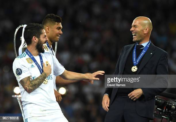 Isco of Real Madrid speaks with Zinedine Zidane Manager of Real Madrid following their sides victory in the UEFA Champions League Final between Real...