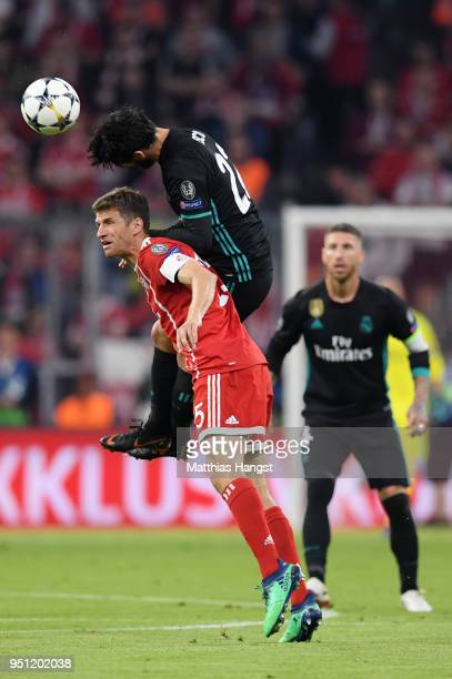 Isco of Real Madrid tackles Thomas Mueller of Bayern Muenchen during the UEFA Champions League Semi Final First Leg match between Bayern Muenchen and...