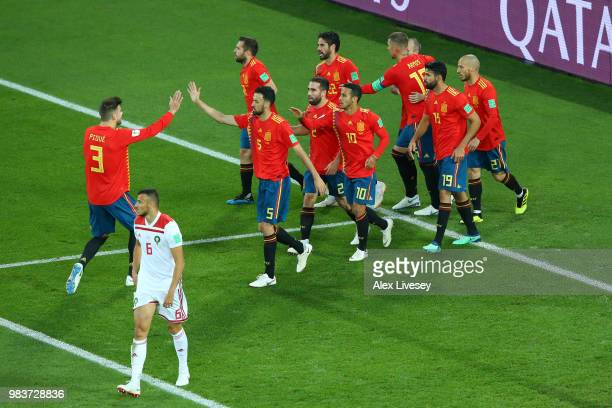 Isco of Spain is congratulated by teammates after scoring his sides opening goal to make the score 11 as Romain Saiss of Morocco walks off dejected...