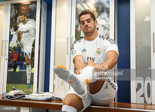 Isco puts on the soccer socks before his official presentation as new Real Madrid player at the Santiago Bernabeu stadium on July 3, 2013 in Madrid,...