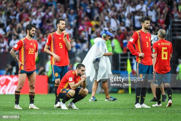 Isco Sergio Busquets and Gerard Pique of Spain dejected during the FIFA World Cup Round of 26 match between Spain and Russia at Luzhniki Stadium on...