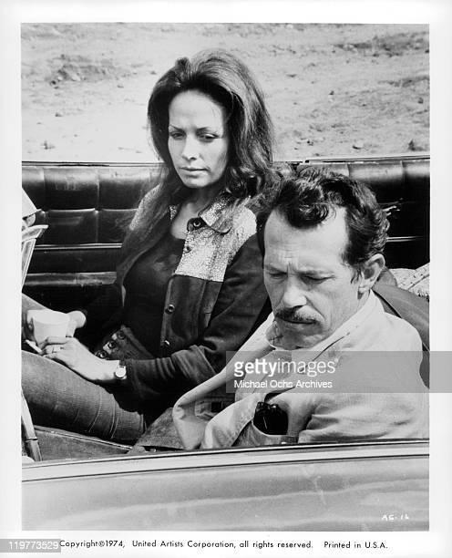 Isela Vega and Warren Oates sitting in car in a scene from the film 'Bring Me the Head of Alfredo Garcia' 1974