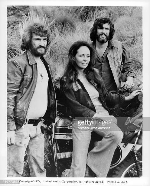 Isela Vega Kris Kristofferson and actor standing next to motorcycle in a scene from the film 'Bring Me the Head of Alfredo Garcia' 1974