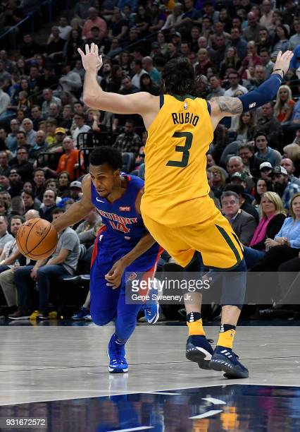 Ish Smith of the Detroit Pistons dives under the defense of Ricky Rubio of the Utah Jazz in the second half of a game at Vivint Smart Home Arena on...