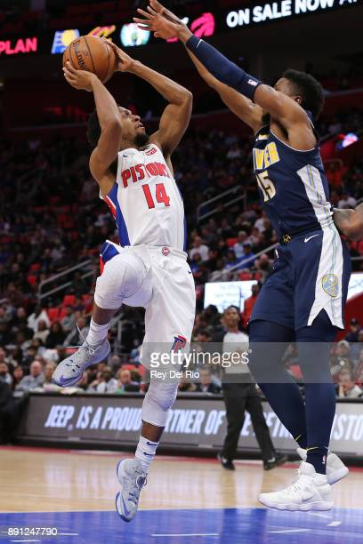 Ish Smith of the Detroit Pistons looks to shoot the ball over Nikola Jokic of the Denver Nuggets at Little Caesars Arena on December 12 2017 in...
