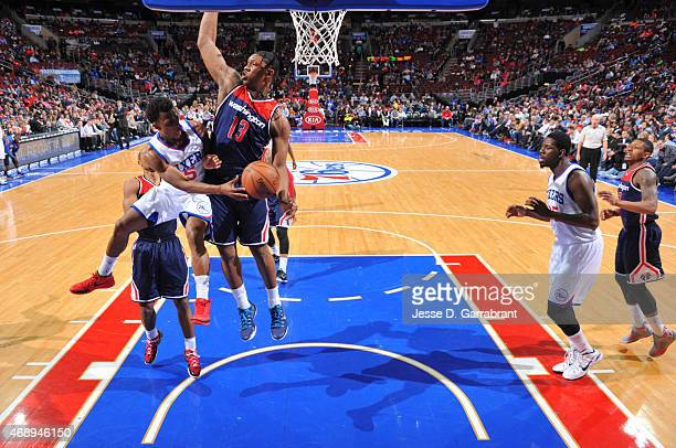 Ish Smith of the Philadelphia 76ers dishes the ball to Henry Sims the Washington Wizards at Wells Fargo Center on April 8 2015 in Philadelphia...