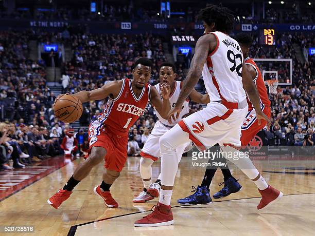 Ish Smith of the Philadelphia 76ers dribbles the ball around Lucas Nogueira of the Toronto Raptors during the first half of an NBA game at the Air...