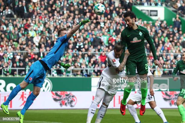 Ishak Belfodil of Bremen and Lukas Hradecky and Marco Russ of Frankfurt compete for the ball during the Bundesliga match between SV Werder Bremen and...