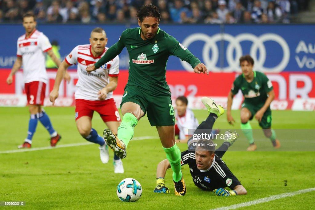 Ishak Belfodil of Bremen (front) fights for the ball with goalkeeper Christian Mathenia of Hamburg during the Bundesliga match between Hamburger SV and SV Werder Bremen at Volksparkstadion on September 30, 2017 in Hamburg, Germany.