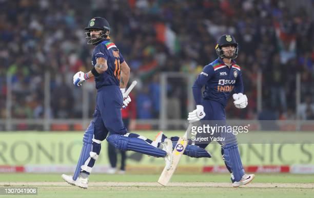 Ishan Kishan and Virat Kohli of India run between the wickets during the 2nd T20 International match between India and England at Narendra Modi...