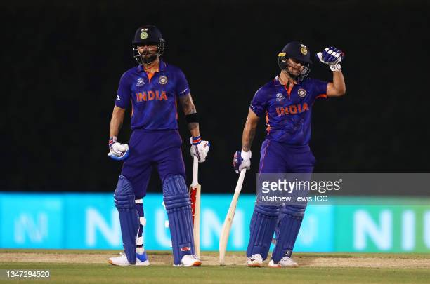 Ishan Kishan of India celebrates their half century with team mate Virat Kohli during the India and England warm Up Match prior to the ICC Men's T20...