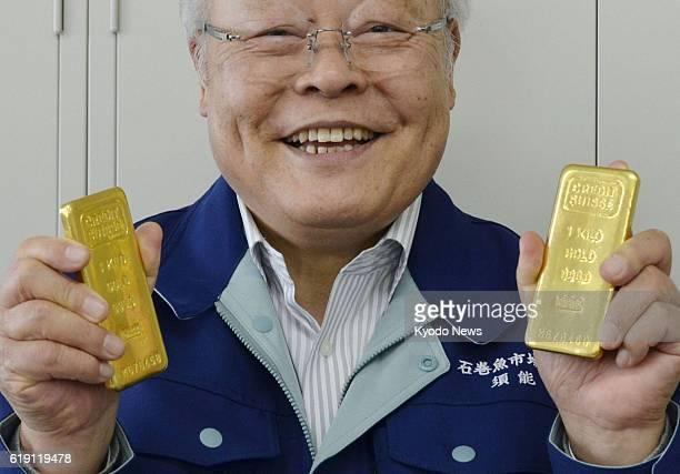 Ishinomaki Japan Kunio Suno president of a fish market in Ishinomaki Miyagi Prefecture holds two gold ingots worth around 10 million yen in total on...