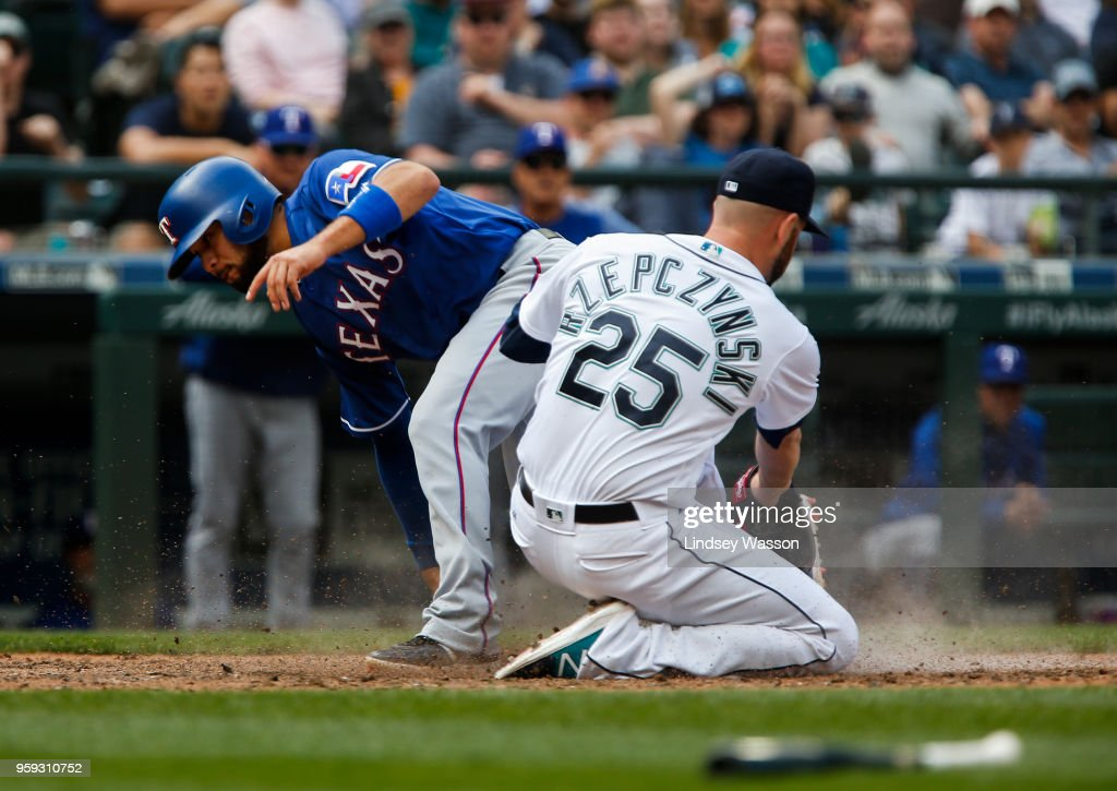 Isiah Kiner-Falefa #9 of the Texas Rangers beats the tag from Marc Rzepczynski #25 of the Seattle Mariners to score in the ninth inning at Safeco Field on May 16, 2018 in Seattle, Washington.