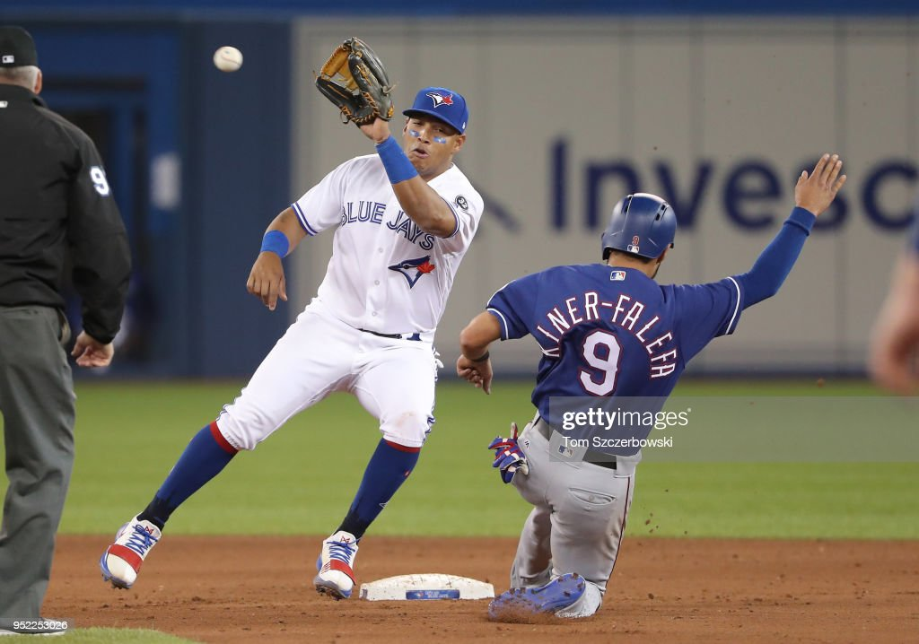 Isiah Kiner-Falefa #9 of the Texas Rangers is caught stealing in the ninth inning during MLB game action as Yangervis Solarte #26 of the Toronto Blue Jays at Rogers Centre on April 27, 2018 in Toronto, Canada.