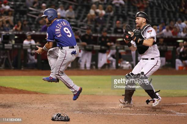Isiah KinerFalefa of the Texas Rangers reacts after safely scoring a run past catch Carson Kelly of the Arizona Diamondbacks during the ninth inning...