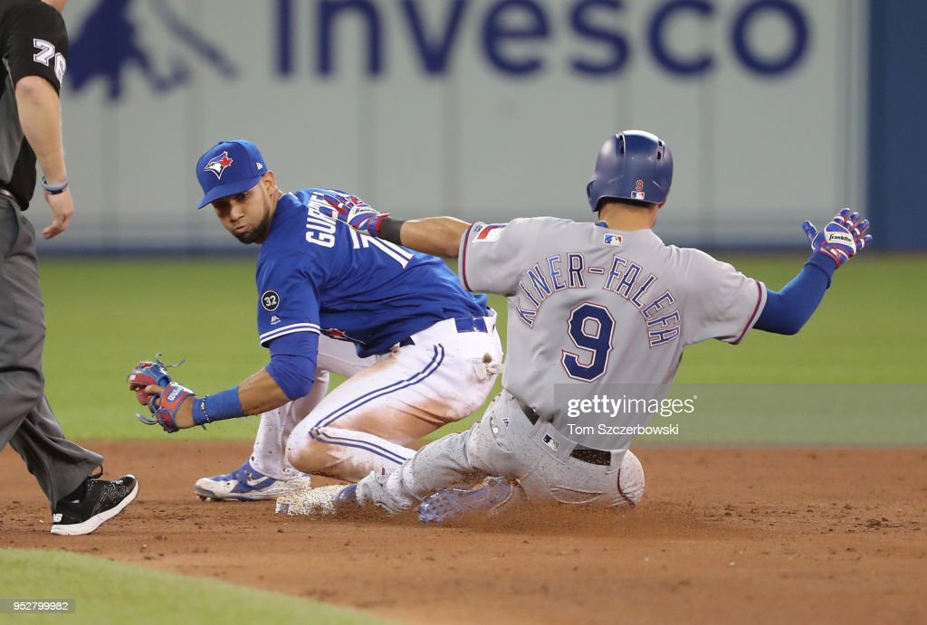 Isiah Kiner-Falefa #9 of the Texas Rangers slides safely into second base with a double in the ninth inning during MLB game action as Lourdes Gurriel Jr. #13 of the Toronto Blue Jays tries to make the tag at Rogers Centre on April 29, 2018 in Toronto, Canada.